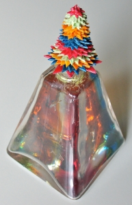 Leo Jean's Starlike© paper sculpture atop glass pyramid filled with colorful resin
